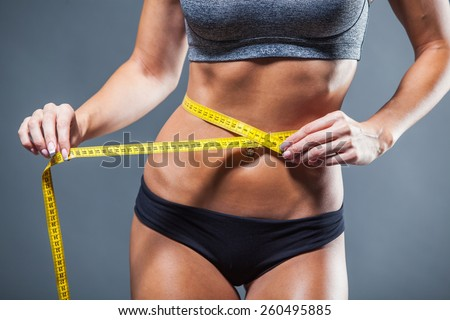 Woman measuring her waist with a yellow measuring tape. - stock photo