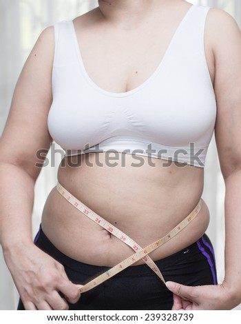 woman measuring waist before fitness
