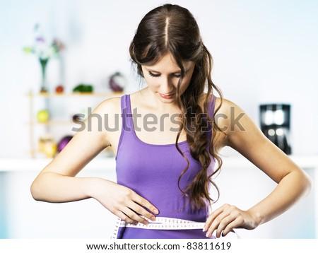 Woman Measuring Waist in kitchen - stock photo