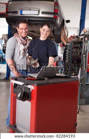 Woman mechanic going over work order on laptop with customer man - stock photo