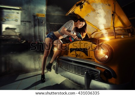 Woman mechanic in sexy shirts is repairing an old car with the screwdriver.