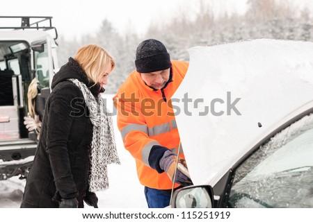 Woman mechanic looking under car hood snow assistance winter broken - stock photo
