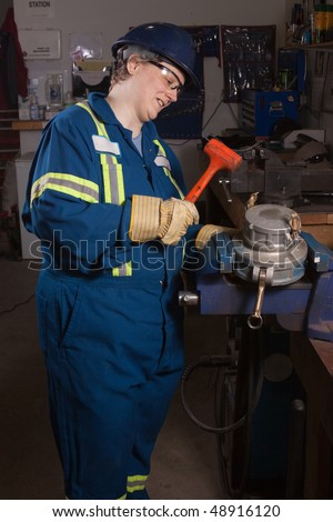 Woman mechanic working in a workshop using a vice grip hammering - stock photo