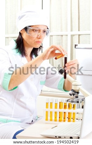 woman medic mix solutions in test tubes, close up - stock photo