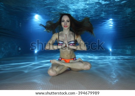 Woman meditate underwater in the pool  - stock photo