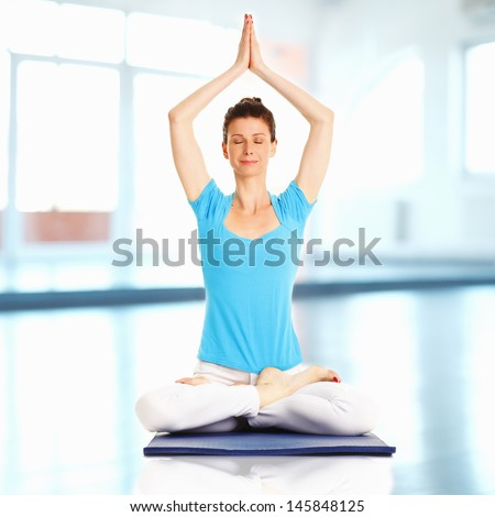 Woman meditating and doing yoga against white background - stock photo
