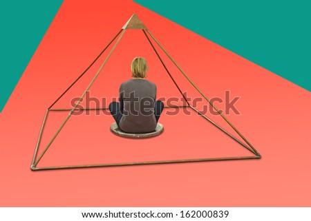Woman meditating and making yoga in metal pyramid - stock photo