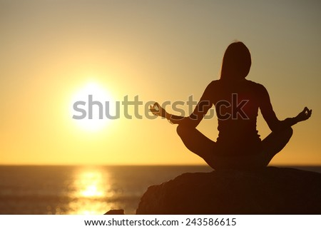 Woman meditating and practicing yoga watching the sun on the beach at sunset - stock photo