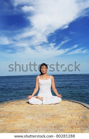 Woman meditating at beach - stock photo