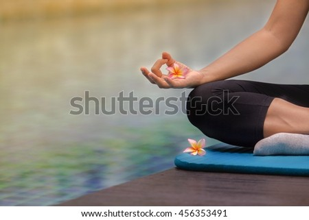 Woman meditating at pool side.(focus on finger and flowers) for background - stock photo