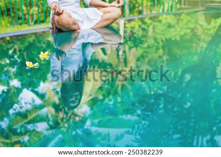 Woman meditating at pool side. Reflection in the water (focus on two floating flowers) - stock photo