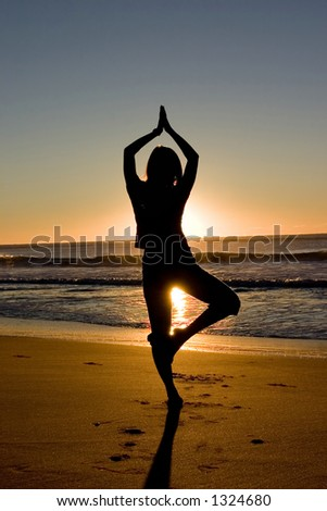 Woman meditating at sunrise - stock photo