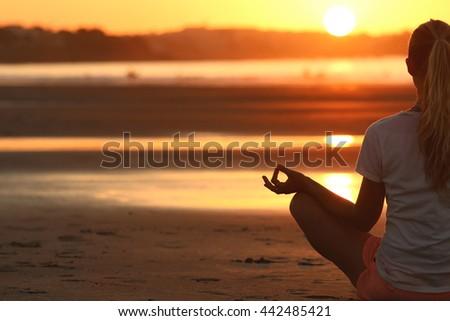 Woman meditating at sunset - stock photo