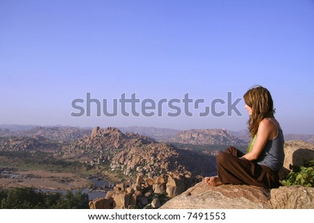 woman meditating at sunset on hilltop in hampi, india - stock photo