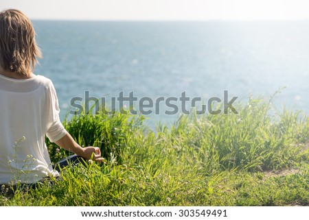 Woman meditating at the sea - stock photo