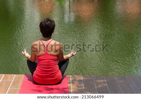 Woman meditating by the pond, rear view - stock photo