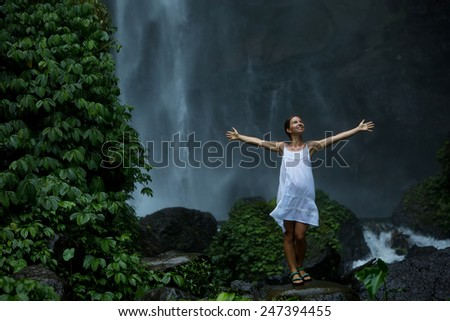 woman meditating doing yoga between waterfalls - stock photo
