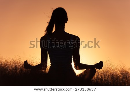 Woman meditating in a peaceful setting.  - stock photo