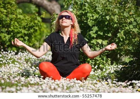Woman meditating in garden between flowers - stock photo