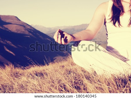 Woman Meditating in Lotus Position on Top of a Mountain - stock photo