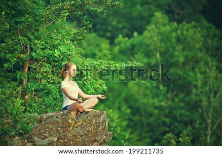 woman meditating in lotus posture, doing yoga on top of the mountain on a rock in nature in the forest - stock photo