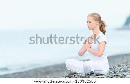 woman meditating in  lotus yoga on  coast of  sea on the beach
