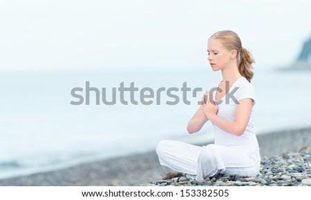 woman meditating in  lotus yoga on  coast of  sea on the beach - stock photo