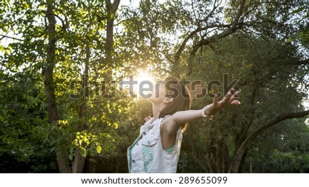 Woman meditating in nature standing with outspread arms as the rising sun touches her face in a woodland setting , upper body in profile.