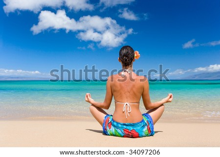 woman meditating in sarong on tropical beach