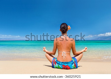 woman meditating in sarong on tropical summer beach relaxing with copy space