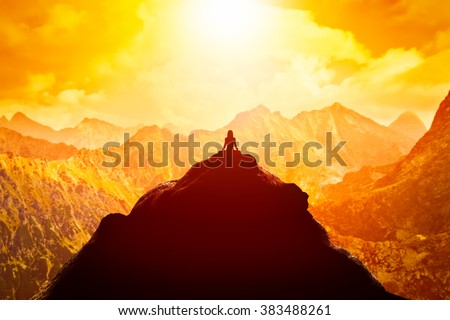 Woman meditating in sitting yoga position on the top of a mountains above clouds at sunset. Zen, meditation, peace - stock photo