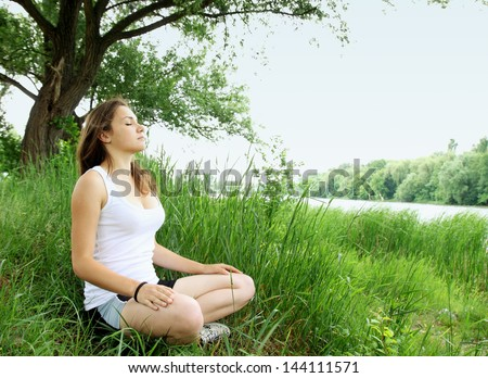 woman meditating in the lotus on the River