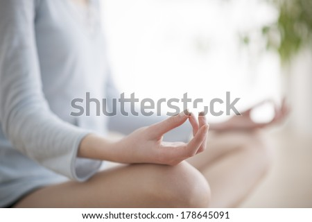Woman meditating in the lotus position closeup - stock photo