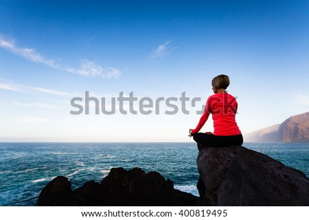 Woman meditating in yoga pose, ocean view, beach and rock mountains. Motivation and inspirational fit and exercising. Healthy lifestyle outdoors in nature concept.
