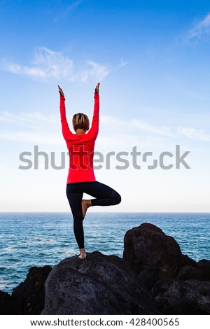 Woman meditating in yoga vrksasana tree pose silhouette at the ocean, beach and rock mountains. Motivation and inspirational fit and exercising. Healthy lifestyle outdoors in nature, fitness concept. - stock photo