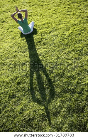 Woman meditating on green grass with a long afternoon shadow - stock photo