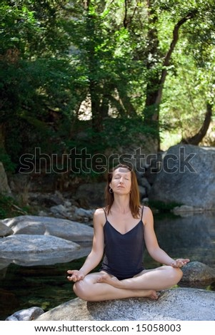 woman meditating on rock river with trees