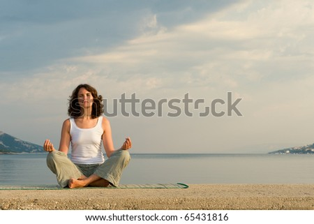 Woman meditating on sea - stock photo