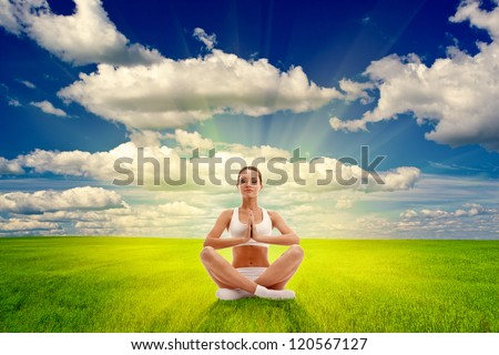 woman meditating on summer field over sunset