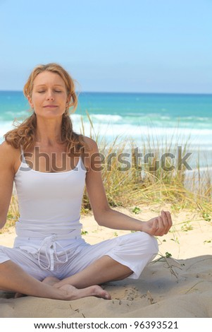 woman meditating on the beach - stock photo