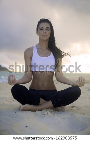 woman meditating on the beach at sunrise - stock photo