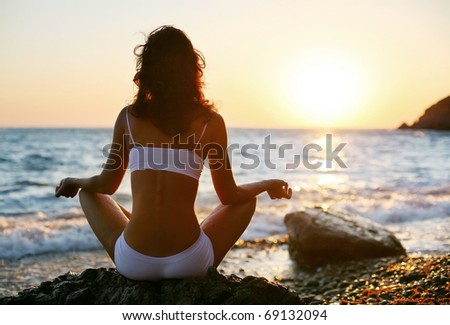 Woman meditating on the beach at sunset. - stock photo