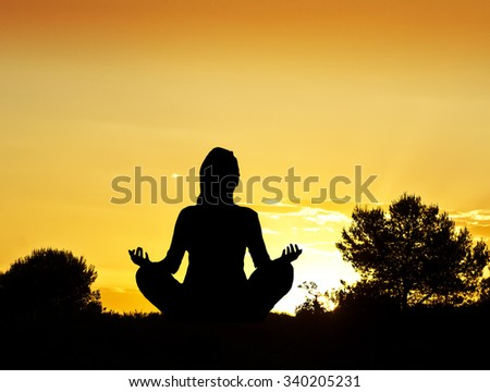 woman meditating on the field - stock photo