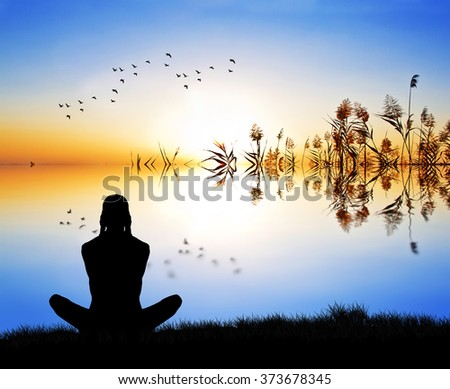 woman meditating waterfront - stock photo
