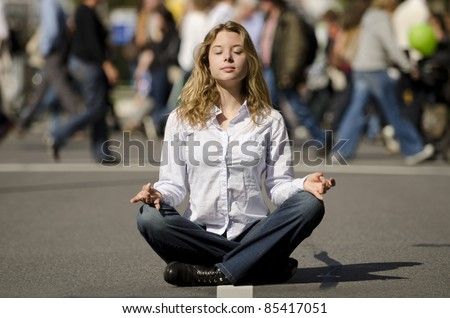 woman meditating yoga in lotus position on busy urban street - stock photo