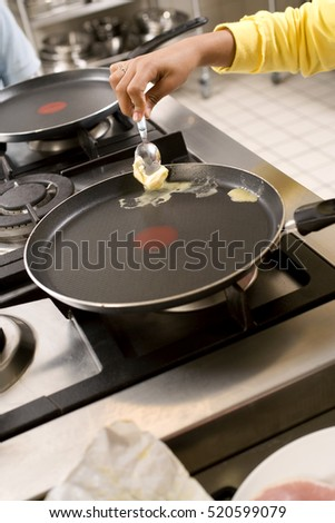 Woman melting the butter in the frying pan