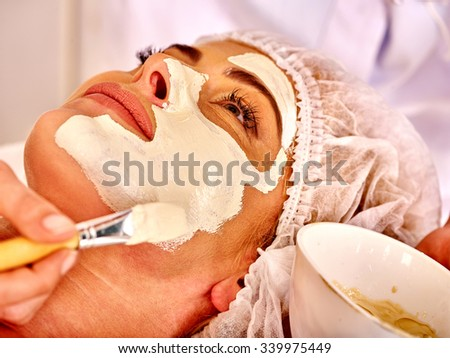 Woman middle-aged take facial and neck clay mask in spa salon.