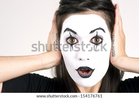Woman Mime entertainer made up in white face frames her features with her hands
