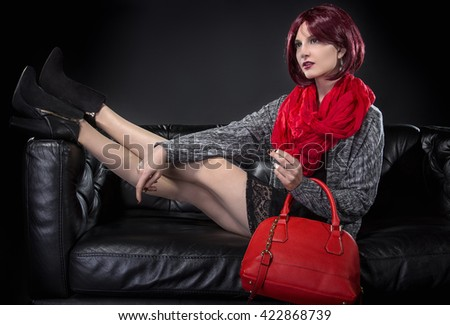 Woman modeling spring fashion and a red hand bag on a black leather couch.  She is wearing fall or spring style fashion. - stock photo