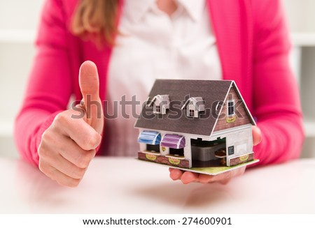 Woman mortgage broker showing thumb up sitting at the desk in office. New house sale and rent.  - stock photo